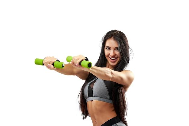 Mooie lachende gespierde fitness vrouw doet oefeningen met halters. portret op een witte achtergrond
