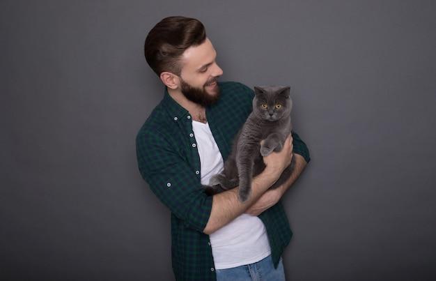 Mooie lachende jonge bebaarde man houdt zijn mooie pluizige kat op handen en ze poseren samen als beste vrienden