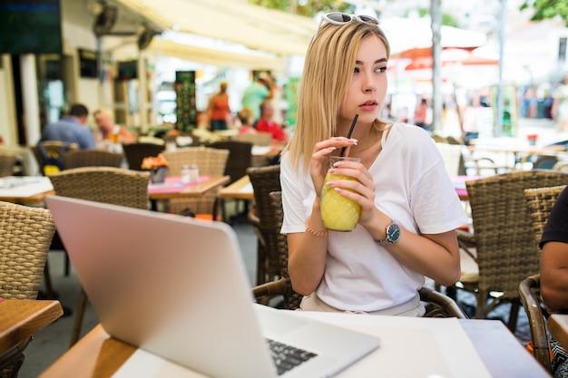 Mooie lachende jonge vrouw buiten zitten en chatten