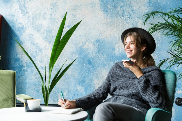 Mooie lachende jonge vrouw gekleed in trui en hoed zittend in de stoel aan de café-tafel, praten op mobiele telefoon, stijlvol interieur, notities maken