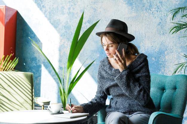 Mooie lachende jonge vrouw gekleed in trui en hoed zittend in de stoel aan de café-tafel, praten op mobiele telefoon, stijlvol interieur