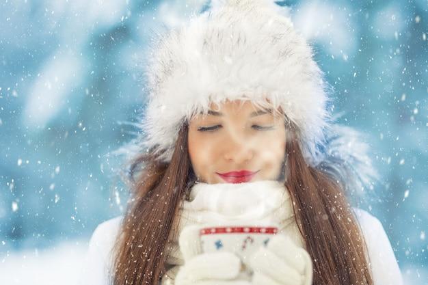 Mooie lachende jonge vrouw in warme kleding met kop warme drank