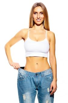 Mooie lachende jonge vrouw met grote jeans, geïsoleerd op wit