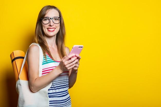 Mooie lachende jonge vrouw met karimat in een zak met een telefoon op een gele achtergrond.