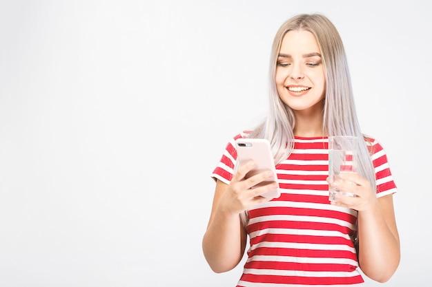Mooie lachende jonge vrouw staat op witte achtergrond en kijkt aan de telefoon met een kopje koud water met een mobiele telefoon. afgelegen, sms'en.