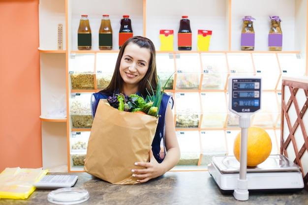 Mooie lachende meisje verkoper achter de toonbank van een groente winkel met een papieren zak met aankopen