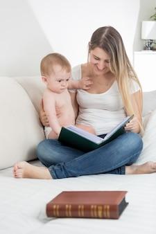 Mooie lachende moeder die afbeeldingen in een oud boek laat zien aan haar 9 maanden oude babyjongen