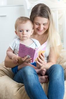 Mooie lachende moeder die een verhaal voorleest aan haar 9 maanden oude babyjongen