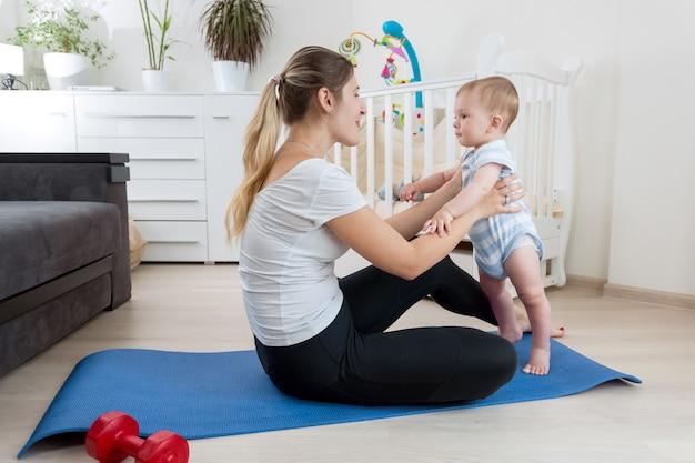Mooie lachende moeder die yoga beoefent op fitnessmat in de woonkamer