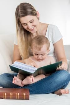Mooie lachende moeder en haar 9 maanden oude babyjongen die op de bank zit en een groot boek leest