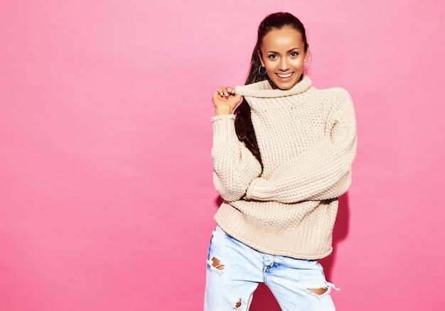 Mooie lachende prachtige vrouw. vrouw die zich in modieuze witte sweater, op roze muur bevindt.