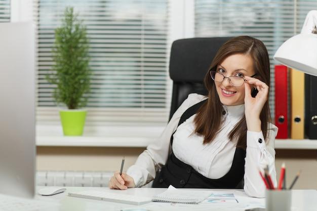 Mooie lachende sexy bruinharige zakenvrouw in pak en bril zitten aan de balie met witte lamp op haar werkplek, werken op computer met moderne monitor met document in licht kantoor