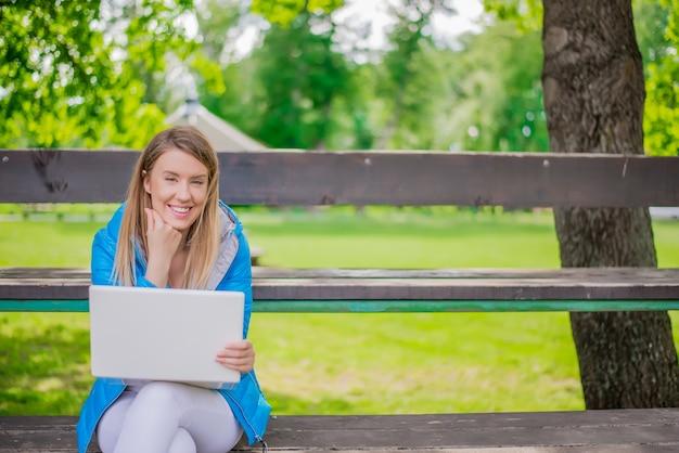Mooie lachende student chatten met vrienden op laptop in de su