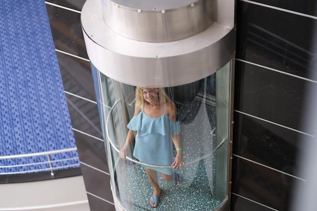 Mooie lachende vrouw eet in transparante lift