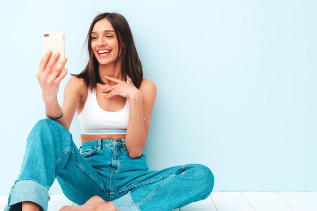 Mooie lachende vrouw gekleed in witte jersey top shirt en jeans. zorgeloos vrolijk model geniet van haar ochtend