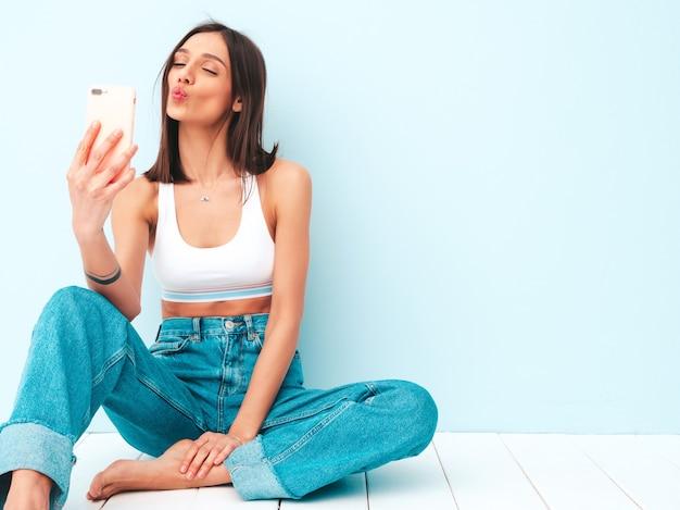 Mooie lachende vrouw gekleed in witte jersey top shirt en jeans. zorgeloos vrolijk model met haar smartphone