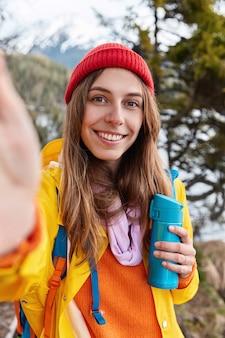 Mooie lachende vrouw houdt onherkenbaar apparaat, maakt selfie, draagt rode hoed en gele jas