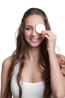 Mooie lachende vrouw houdt wattenschijfje geïsoleerd op een witte achtergrond. meisje dat haar gezicht schoonmaakt