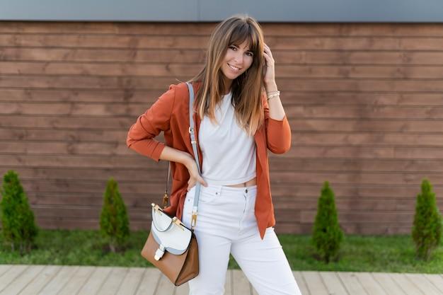 Mooie lachende vrouw in jas poseren in de stad.