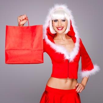 Mooie lachende vrouw in sneeuw maiden pak houdt de boodschappentassen