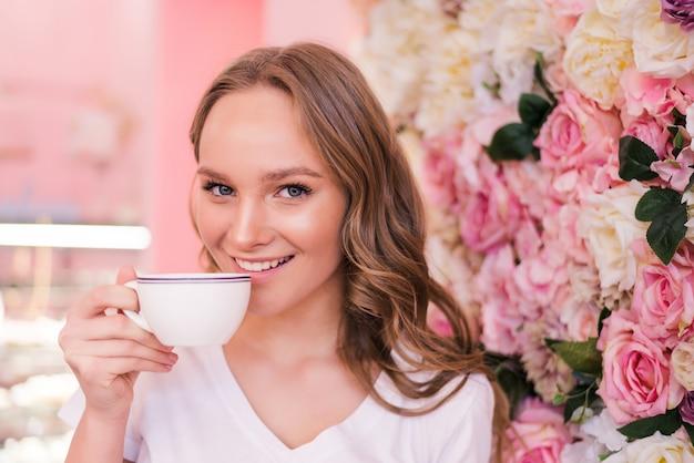 Mooie lachende vrouw koffie drinken in café. portret van een rijpe vrouw in een cafetaria die hete thee drinkt. mooie vrouw met kop koffie.