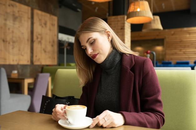 Mooie lachende vrouw koffie drinken in café.