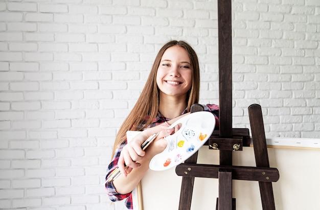 Mooie lachende vrouw kunstenaar met kleurenpalet en penselen