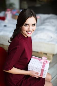Mooie lachende vrouw met cadeau thuis.