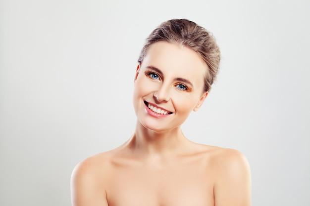 Mooie lachende vrouw met heldere huid en schattige glimlach. spa- en huidverzorgingsconcept