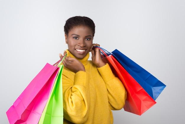 Mooie lachende vrouw met kleurrijke boodschappentassen op schouders