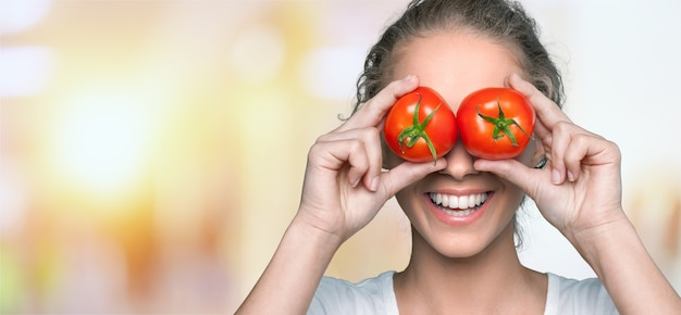 Mooie lachende vrouw met twee rijpe tomaten
