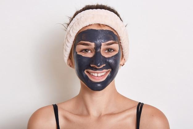 Mooie lachende vrouw met zwarte klei gezichtsmasker op gezicht, camera kijken met gelukkige uitdrukking, met haarband op haar hoofd, poseren geïsoleerd op witte achtergrond.