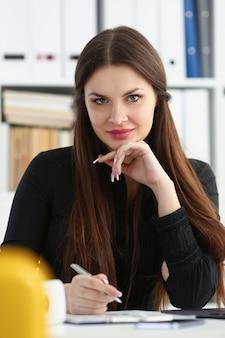 Mooie lachende vrouw op de werkplek met zilveren pen in de camera kijken