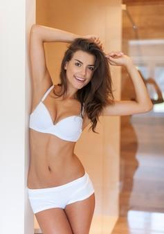 Mooie lachende vrouw poseren in ondergoed