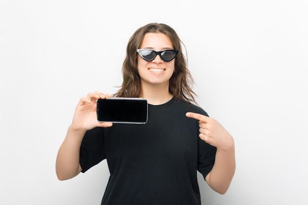 Mooie lachende vrouw wijst naar het scherm van de telefoon die ze vasthoudt.