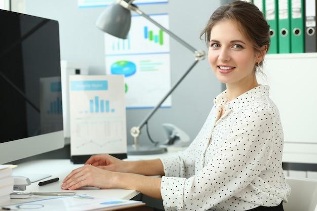 Mooie lachende vrouw zitten in kantoor
