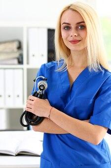 Mooie lachende vrouwelijke arts staan in kantoor met stethoscoop portret. lichamelijk, examen, eh, ziektepreventie, afdelingsronde, patiëntbezoekcontrole, 911, remedie voorschrijven, concept voor gezonde levensstijl
