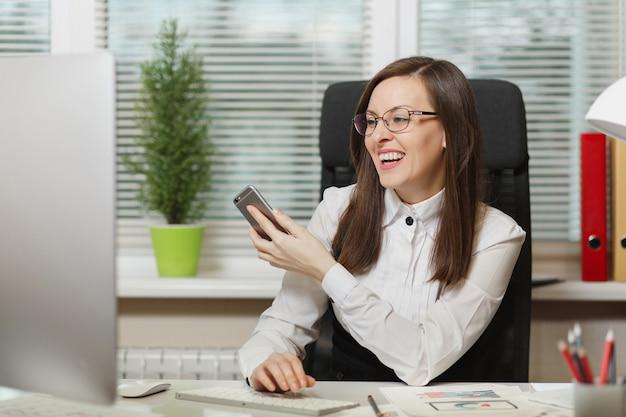 Mooie lachende zakenvrouw in pak en bril zitten aan de balie, werken op hedendaagse computer met documenten in lichte kantoor, praten op mobiele telefoon, aangenaam gesprek voeren