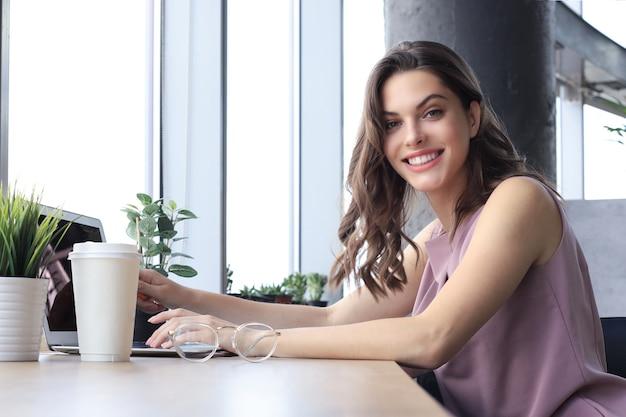 Mooie lachende zakenvrouw zit op kantoor en kijkt naar de camera.