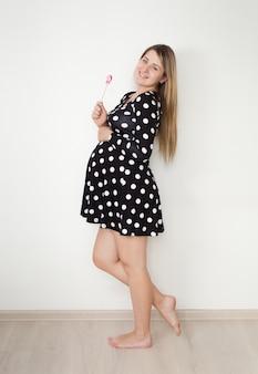 Mooie lachende zwangere vrouw in schattige jurk poseren met lolly