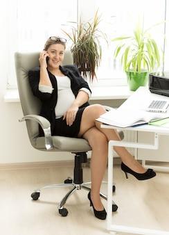 Mooie lachende zwangere vrouw praten over de telefoon op kantoor