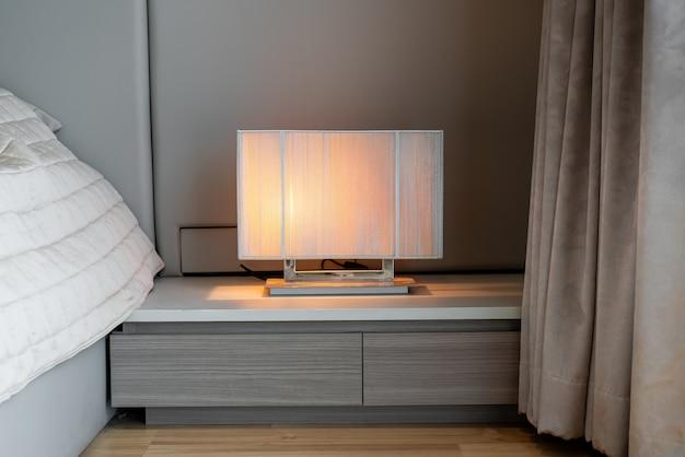Mooie lamp naast beddecoratie in slaapkamer