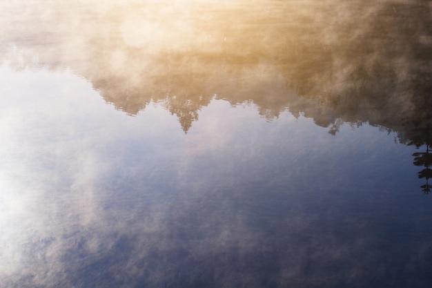 Mooie landschapshemel van mist en mist over het meer en zonsopgang die met blauwe hemelbezinning glanzen over het wateroppervlak bij het dorp van de heuvelstam op berg in thailand