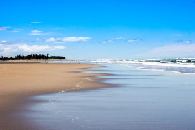 Mooie landschapsmening van leeg zeestrand onder de helderblauwe hemel