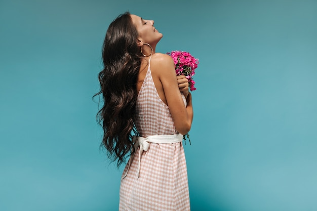 Mooie lang donkerharige slanke vrouw met tatoeage in stijlvolle zomerjurk met brede witte riem poseren met roze bloemen op blauwe muur