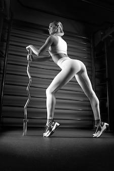 Mooie lange blonde poseren in de sportschool met een barbell in haar handen tegen de achtergrond van de muurbar. het concept van sport, fitness, aerobics, bodybuilding, stretching. achteraanzicht. gemengde media