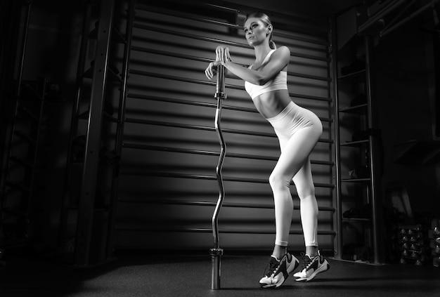 Mooie lange blonde poseren in de sportschool met een barbell in haar handen tegen de achtergrond van de muurbar. het concept van sport, fitness, aerobics, bodybuilding, stretching. zijaanzicht. gemengde media