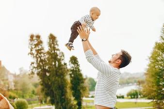 Mooie lange en stijlvolle vader in een trui en een spijkerbroek beukt met zijn kleine lieve zoon