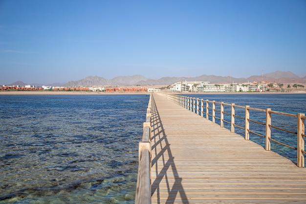 Mooie lange houten pier tussen de oceaan en de bergen.