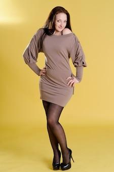 Mooie lange vrouw in een beige jurk poseren